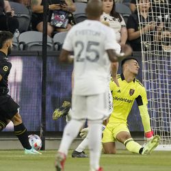 Los Angeles FC forward Diego Rossi, left, scores on Real Salt Lake goalkeeper David Ochoa, right, as midfielder Everton Luiz watches during the first half of a Major League Soccer match Saturday, July 17, 2021, in Los Angeles.