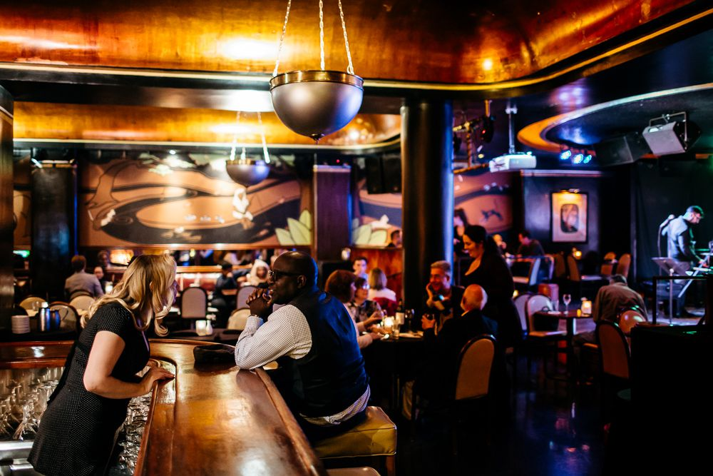 A Man sits at the bar in a jewel-toned art deco bar.