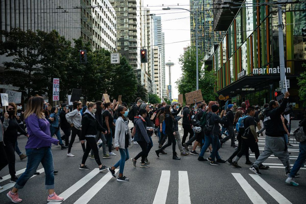 A protest march in downtown Seattle with the Space Needle in the background, as well as the restaurant Marination