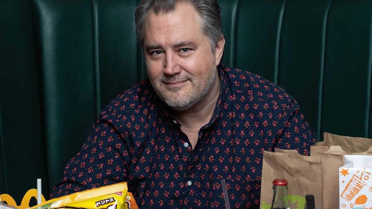 A man in a button-up shirt sits in a green booth surrounded by bags of chips, sodas, Duke's mayo, pork rinds, and other snacks