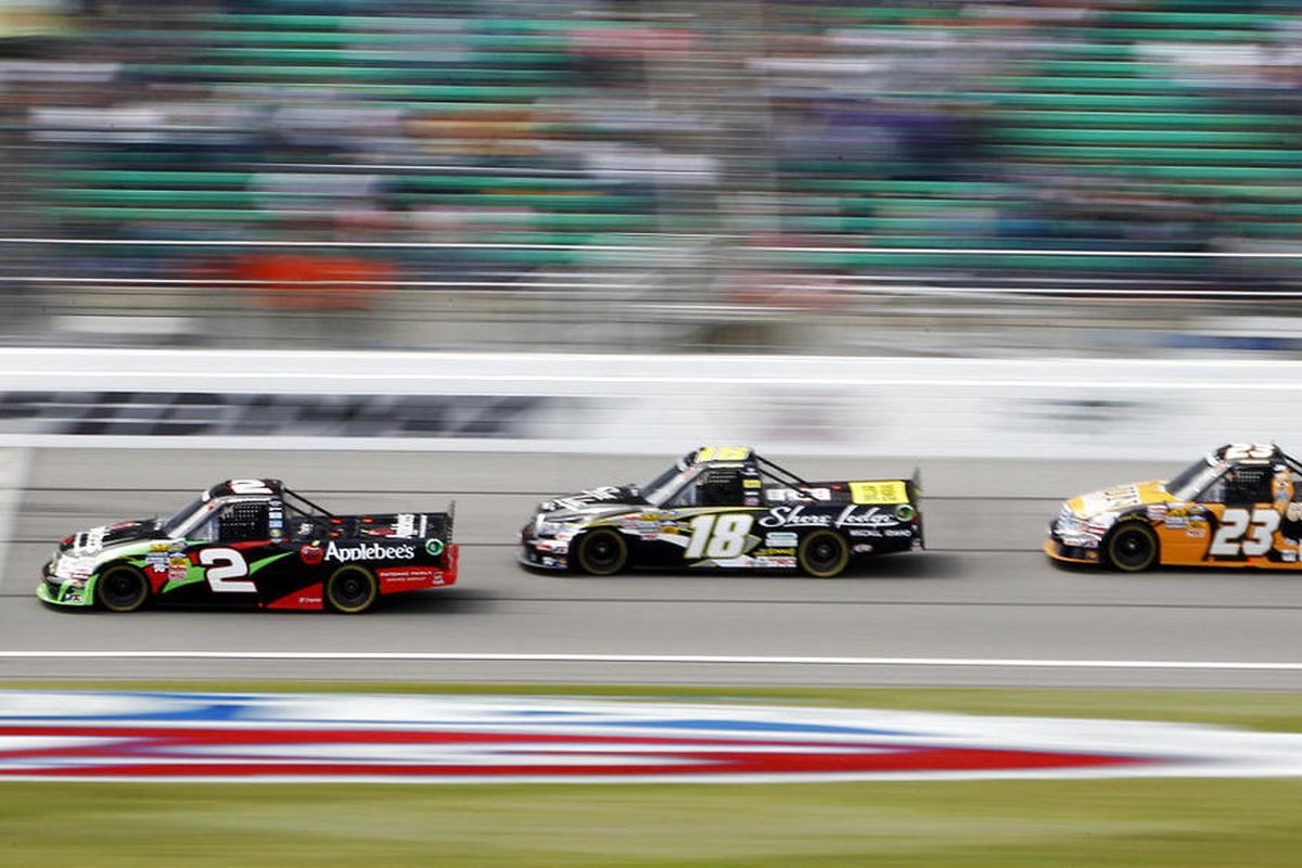 Tim George Jr. (2) leads Jason Leffler (18) and Jason White (23) into the first lap of the NASCAR Truck Series auto race at Kansas Speedway in Kansas City, Kan., Saturday, April 21, 2012. (AP Photo/Orlin Wagner)