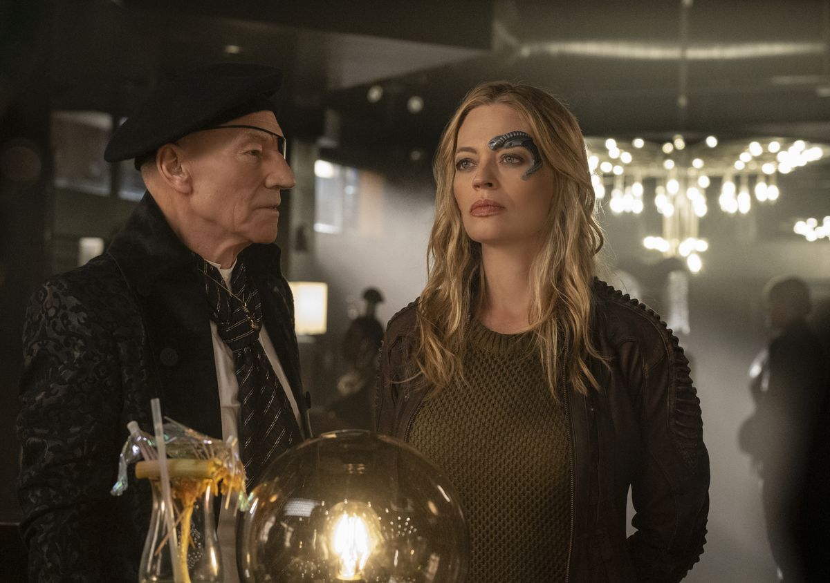 Patrick Stewart as Jean-Luc Picard, in disguise as an eyepatched slaver, pretends to menace Jeri Ryan as Seven of Nine on Star Trek: Picard.