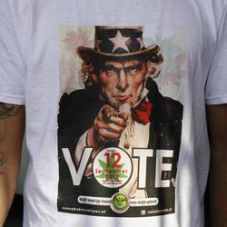 """In this photo taken Monday Sept. 3, 2012, a worker at Cafe Cremers coffee shop in The Hague, Netherlands, who does not want to be identified, wears a T-shirt urging people to vote against the country's """"weed pass"""" system in the upcoming Sept. 12 election.  With slogans like """"Don't let your vote go up in smoke!'', owners of the free-wheeling cafes where bags of hashish are sold alongside cups of coffee are mounting a get-out-the-stoner-vote campaign to encourage the drugged up stoned voters ahead of next week's Dutch election. The campaigners are calling on their sometimes apathetic dope smoking clientele to get out and support political parties that oppose the recently introduced """"weed pass"""" that is intended to rein in the cafes."""