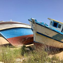 Old boats used by smugglers to bring refugees to Italy sit idle on the shores of Lampedusa. Refugee traffickers now resort to using large inflatable rafts, forgoing the expense of boats and the engines and fuel to power them.
