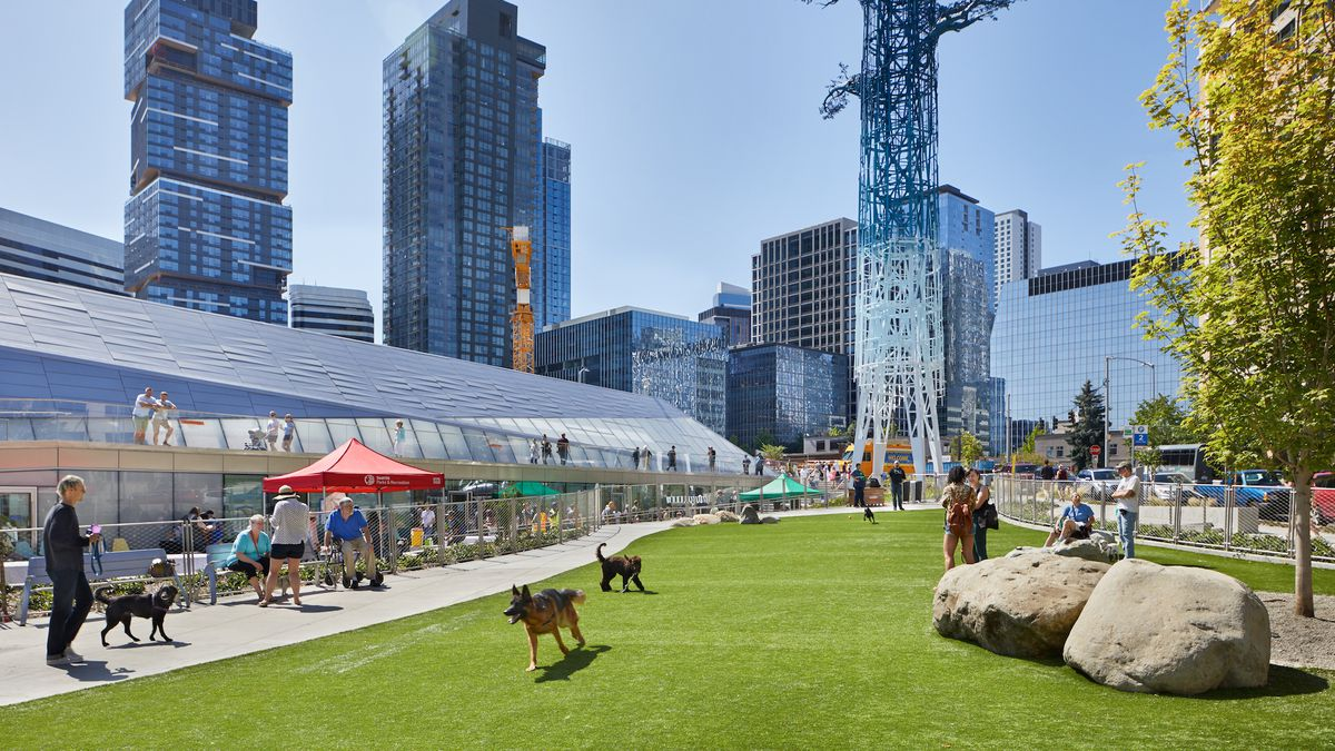 A modern electrical substation with a dog park and public promenade around it.