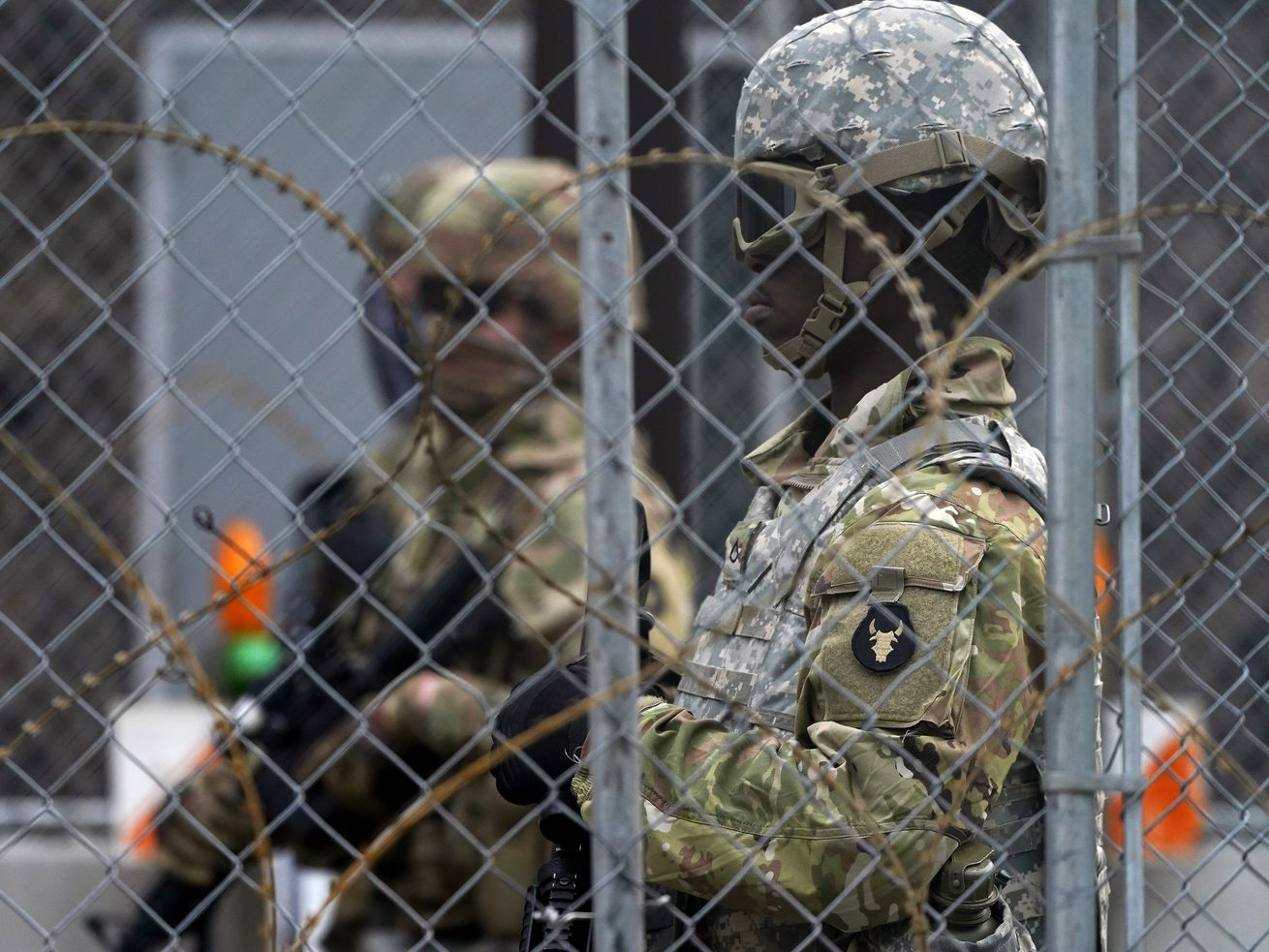 National Guard members are seen through fencing and wire near the Minneapolis Police 3rd Precinct in Minneapolis on Monday, April 19, 2021, after the murder trial against former Minneapolis police Officer Derek Chauvin advanced to jury deliberations.