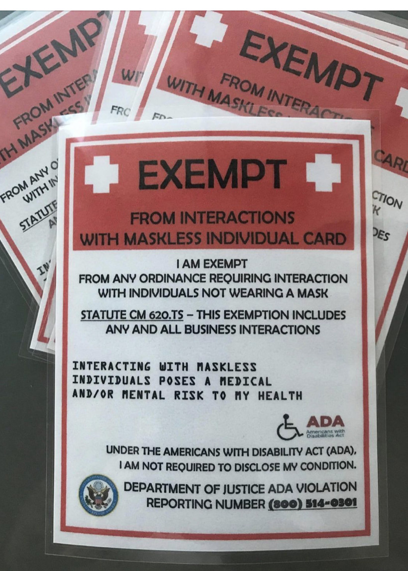 A photo of a stack of laminated badges warning folks of mask interaction exemptions.