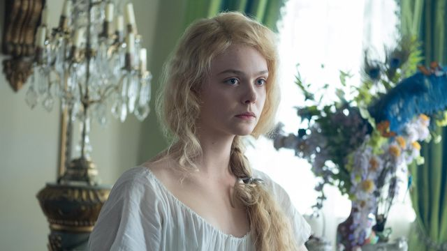 Elle Fanning as Catherine the Great sits in a flimsy white nightgown with her hair hanging over her shoulders in The Great.