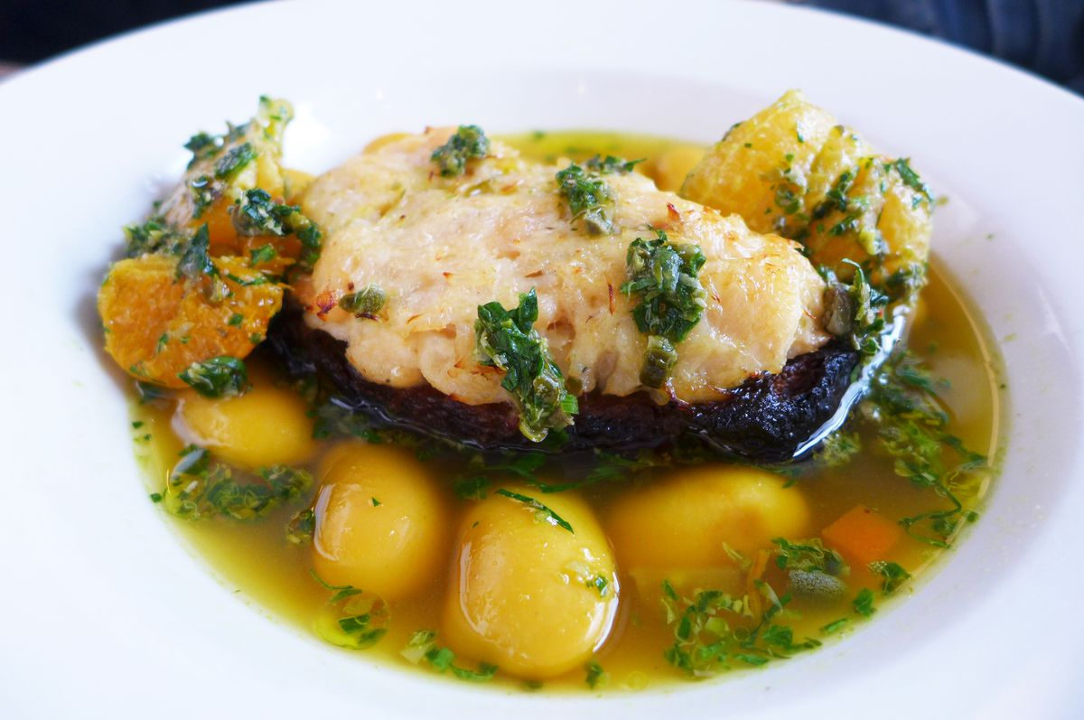 A plank of fish on a dark bread toast in broth with giant white beans.