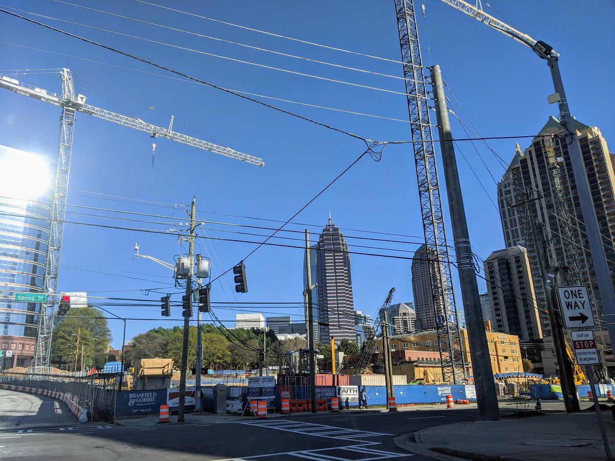 A huge construction site with cranes under a blue sky.