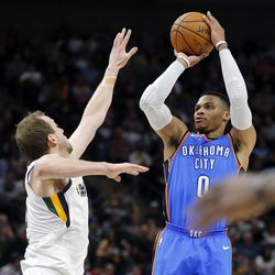 Oklahoma City Thunder guard Russell Westbrook takes a shot with Utah Jazz forward Joe Ingles defending during NBA basketball in Salt Lake City on Saturday, Dec. 23, 2017.