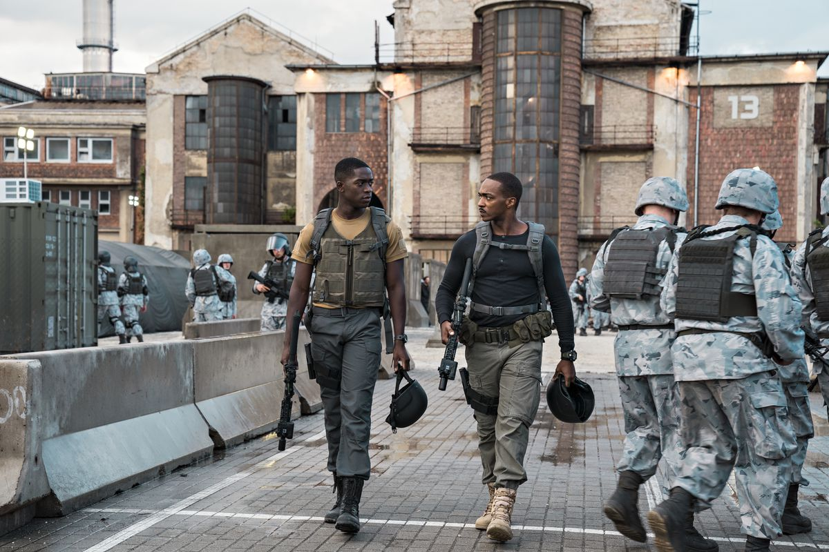 Damson Idris as Harp and Anthony Mackie as Leo walk through a crowd of soldiers while holding helmets and guns in Outside the Wire