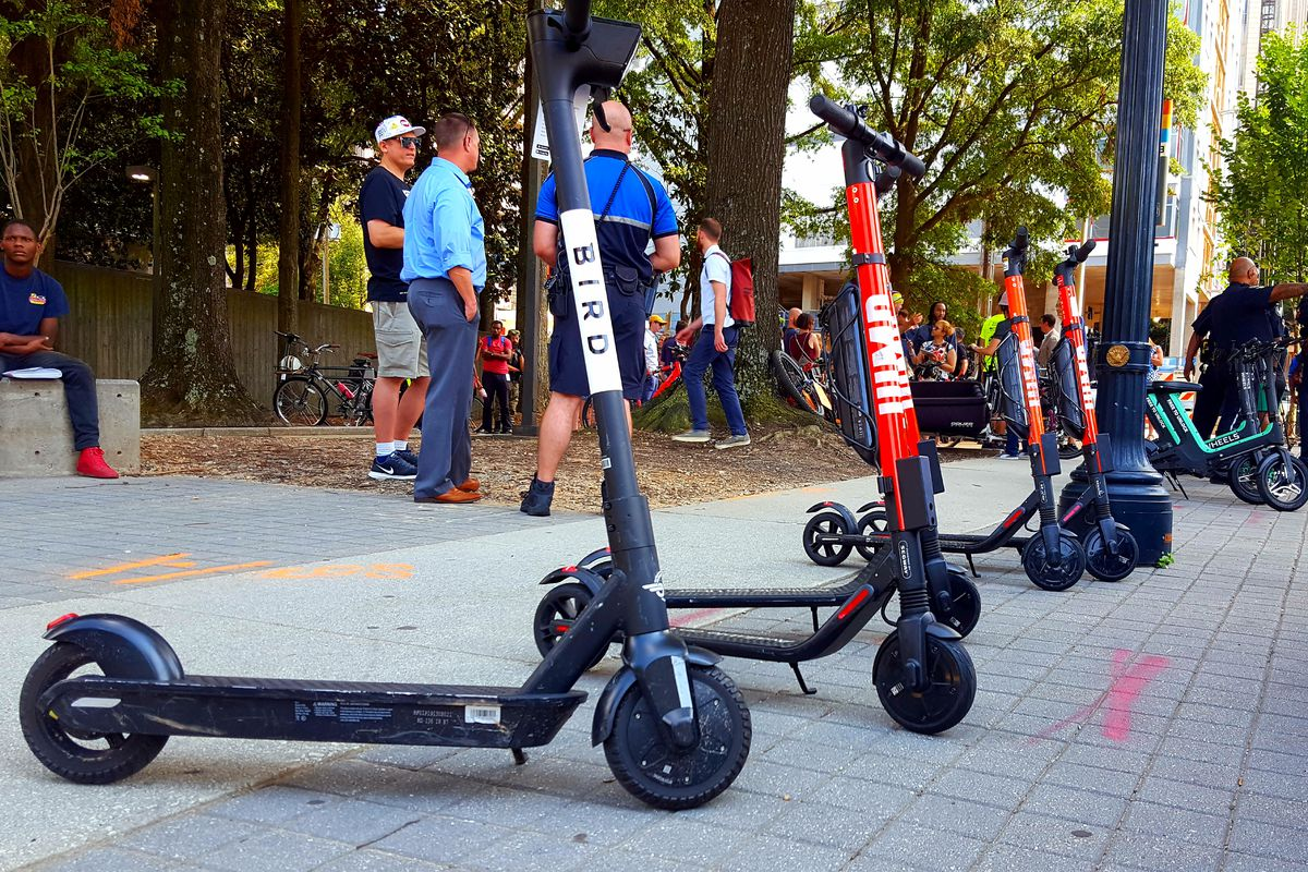 A picture of e-scooters lining a sidewalk in front of a crowd of people at a MARTA station.