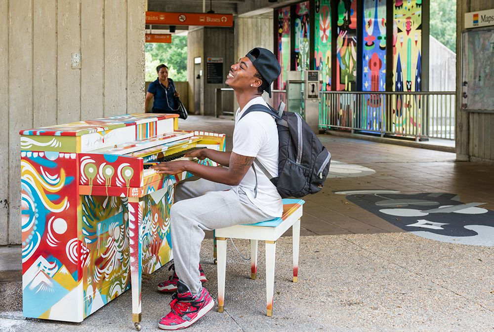 A young man plays the vibrantly decorated piano outside the Arts Center MARTA station.