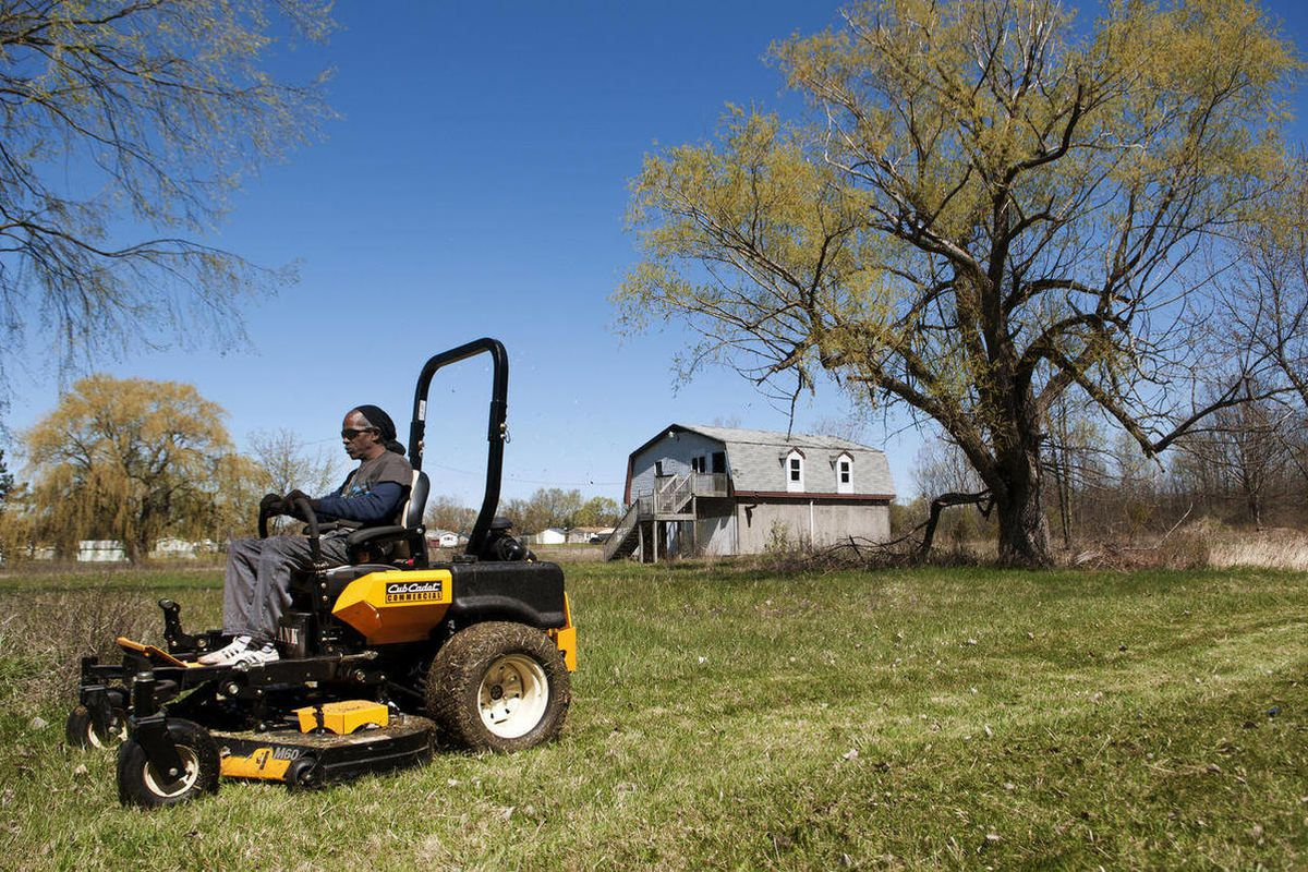 ADVANCE FOR MONDAY APRIL 23 - In this April 6, 2012 photo, Jackie King mows the lawn of a 2.7 acre lot in Mount Morris Township, Mich.  Next to a burned-down house, vacant lots and dilapidated homes will soon stand rows among rows of fruit trees _ 200 of