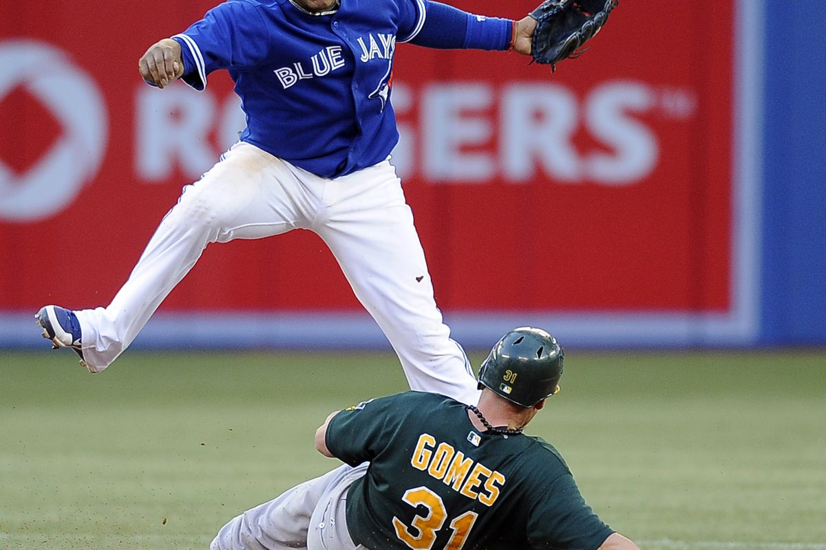 TORONTO, CANADA - JULY 24:  Yunel Escobar #5 of the Toronto Blue Jays jumps over a sliding Jonny Gomes #31 of the Oakland Athletics during MLB game action July 24, 2012 at Rogers Centre in Toronto, Ontario, Canada. (Photo by Brad White/Getty Images)