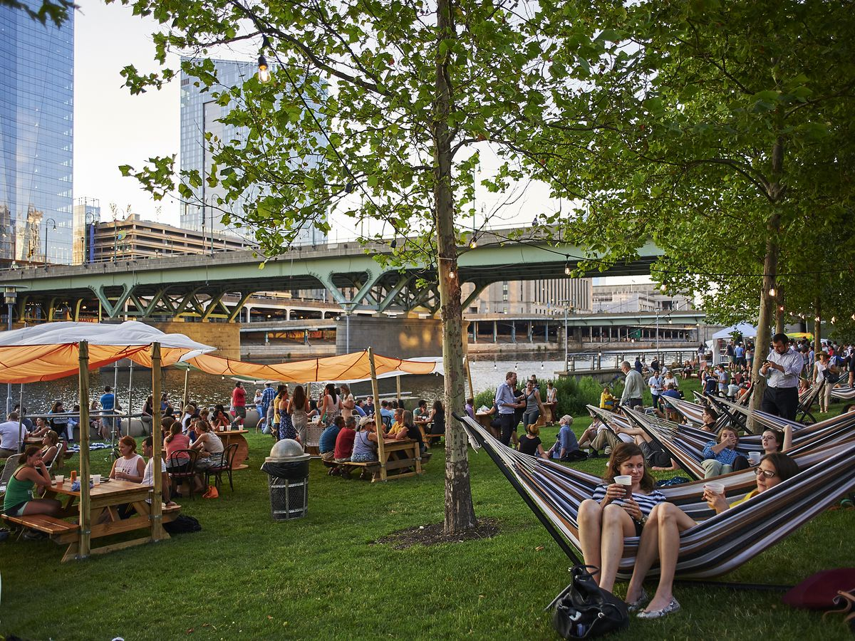 Crowds of people in hammocks and picnic tables on the Schuylkill River Banks during Parks on Tap.
