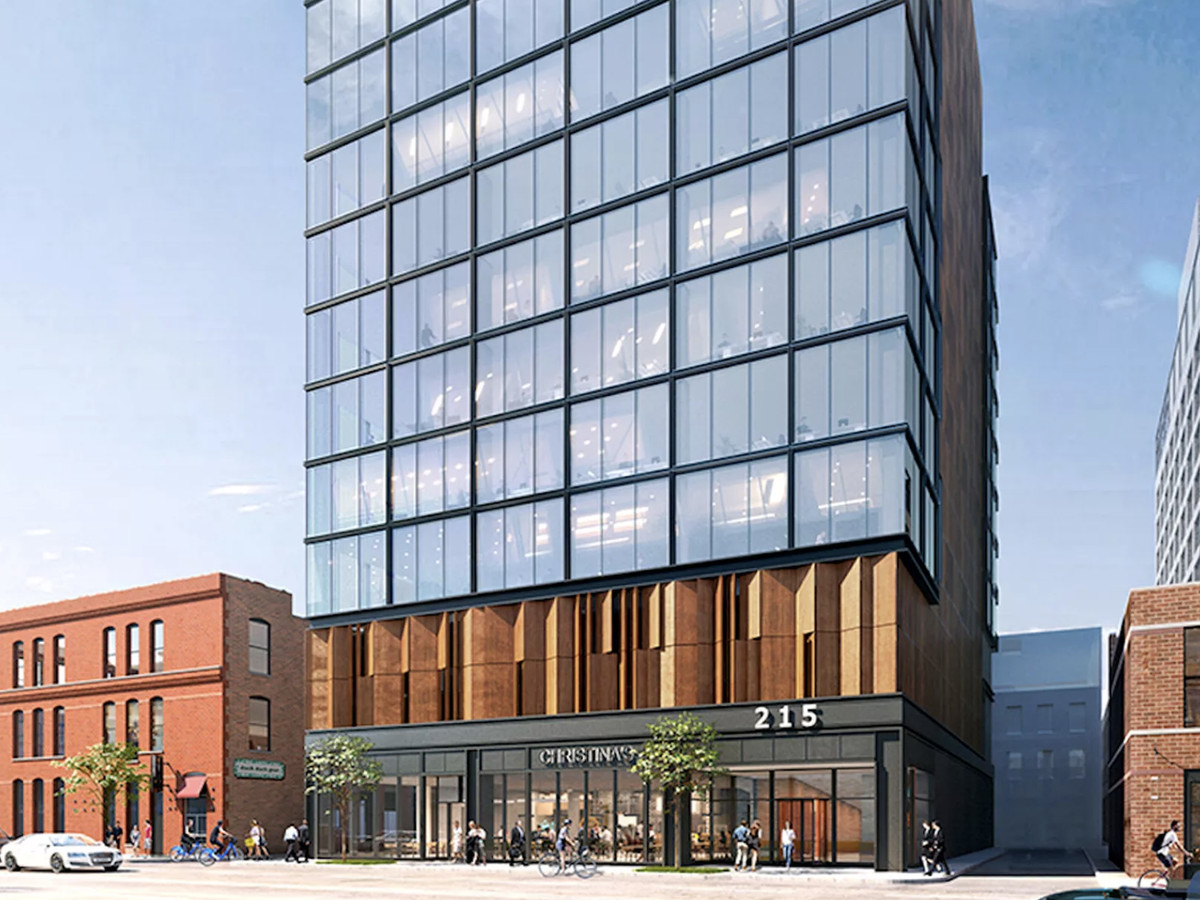 A narrow brick, metal, and glass office tower with a lobby and retail space along the sidewalk. Bronze metal panels cover the second and third floor parking garage below glass-clad office levels.