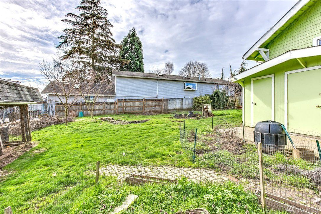 The backyard of a green house has a chicken coop