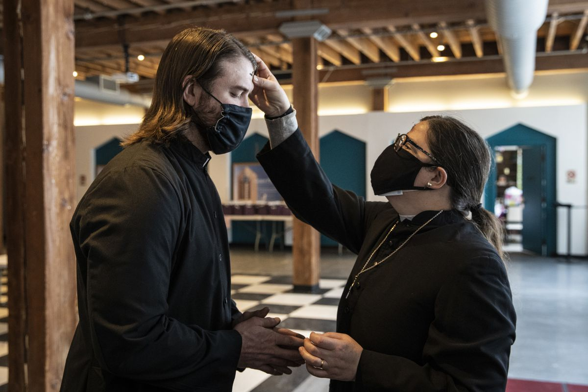 Pastor Ben Adams, of Holy Trinity Lutheran Church, receives the imposition of ashes from the Rev. Amity Carrubba at Grace Episcopal Church of Chicago in the South Loop on Ash Wednesday.