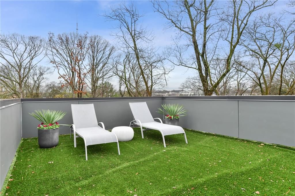 A carpeted roof deck area with two white chairs.
