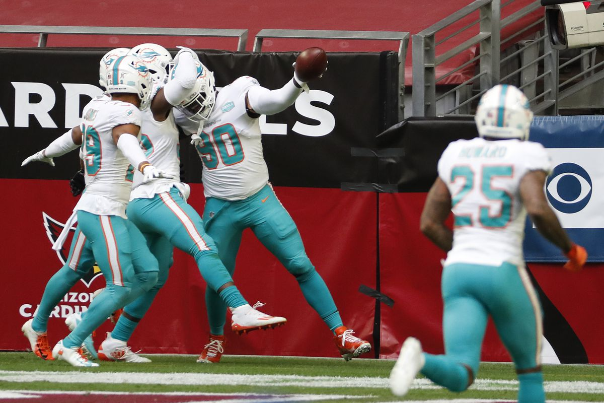 Shaq Lawson #90 of the Miami Dolphins celebrates with Brandon Jones #29 and Jerome Baker #55 after recovering a fumble for a touchdown during the first half against the Arizona Cardinals at State Farm Stadium on November 08, 2020 in Glendale, Arizona.