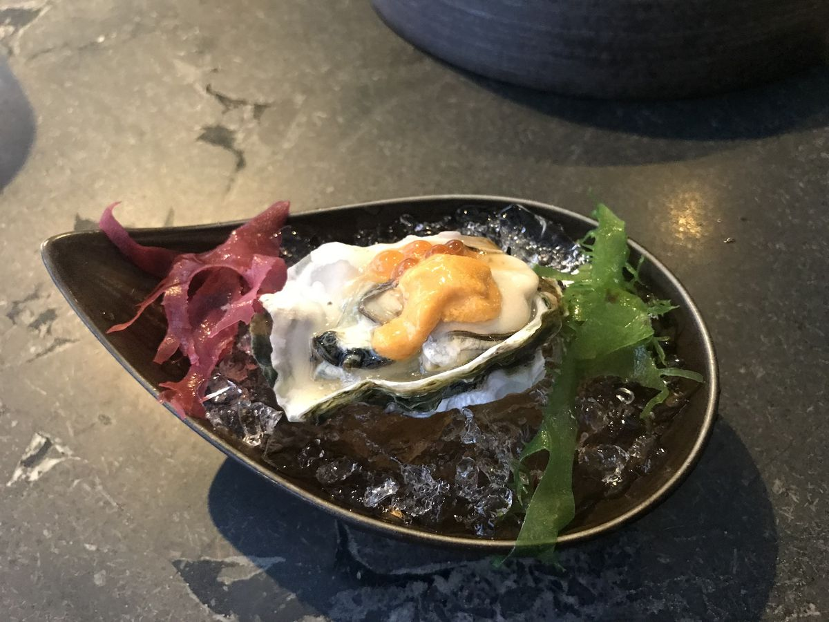 A raindrop-shaped metal bowl holding an oyster topped with uni on a bed of crushed ice and seaweed.