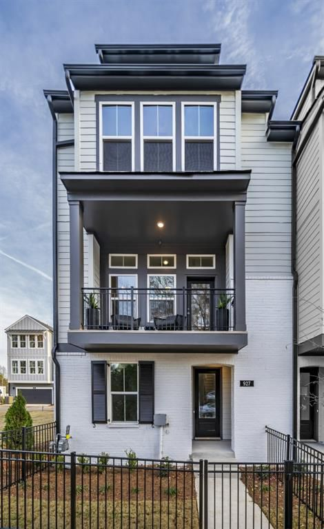 A white and gray exterior of a tall townhome with a patio.