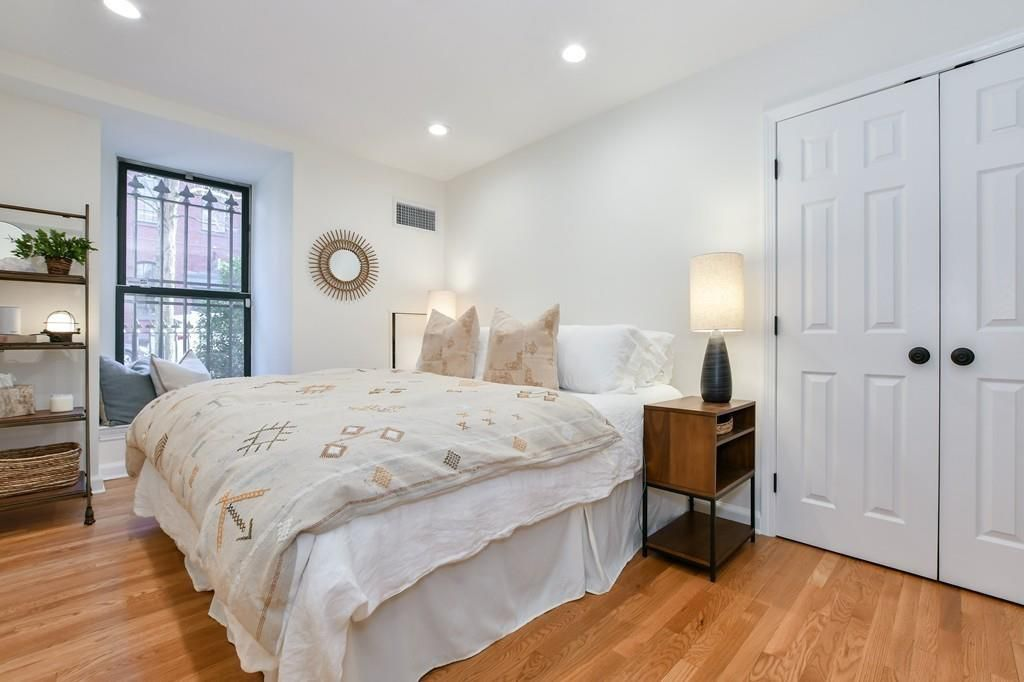 A bedroom with a bed and a double-door closet.