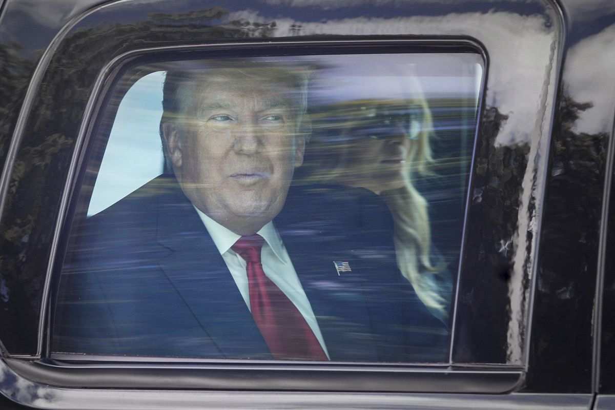 Former President Donald Trump and former first lady Melania Trump ride in a motorcade through West Palm Beach, Fla., on their way to his Mar-a-Lago club in Palm Beach after arriving from Washington aboard Air Force One on Wednesday, Jan. 20, 2021.