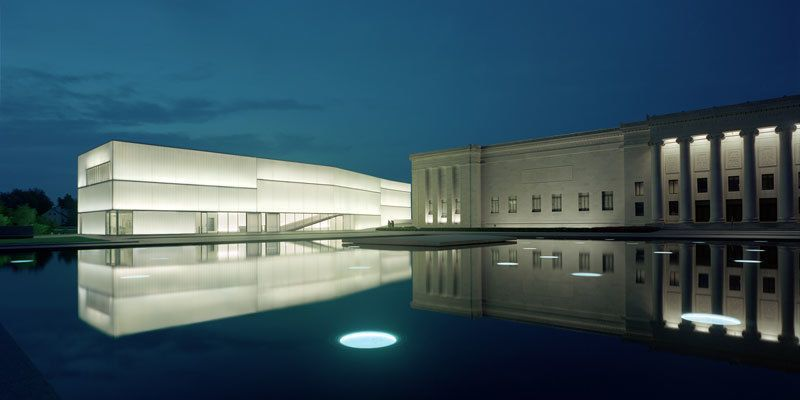 The exterior of the Nelson Atkins Museum of Art in Missouri. The facade is white with translucent glass and there is a pond surrounding the building. It is night and the lights inside the museum are illuminating the exterior.