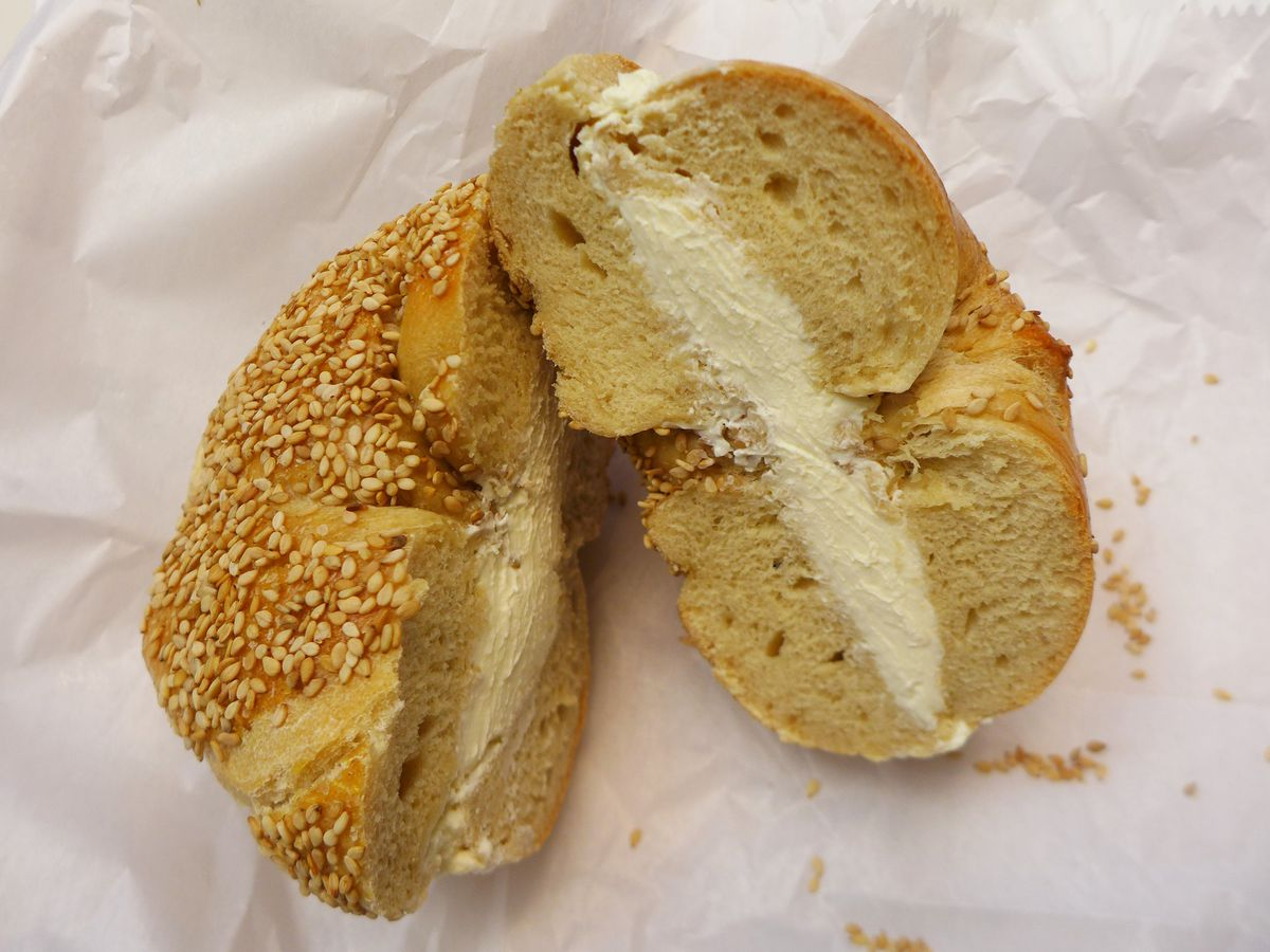 A sesame seed bagel split and slathered with cream cheese.