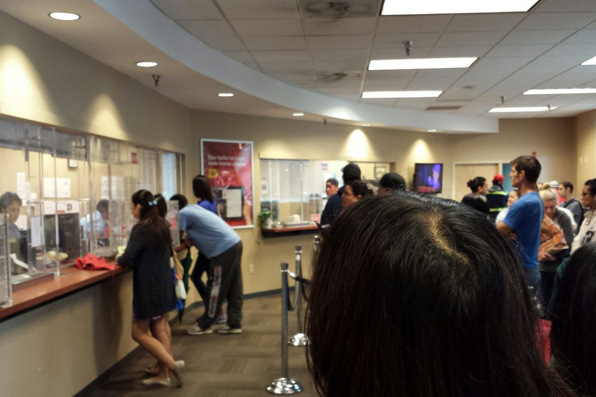Customers wait in line at the Comcast Customer Service Center in Washington DC.