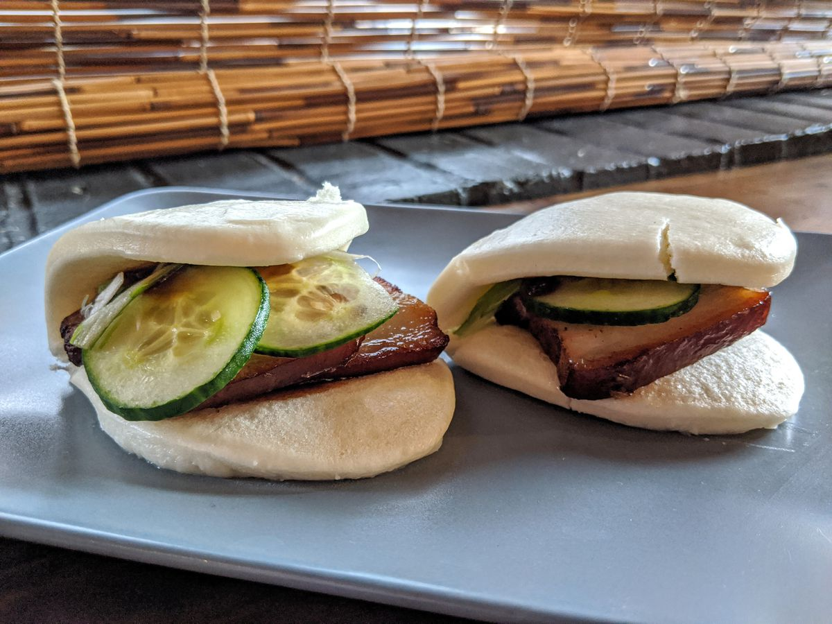 Two pork belly buns, topped with sliced cucumber, sit on a blue plate