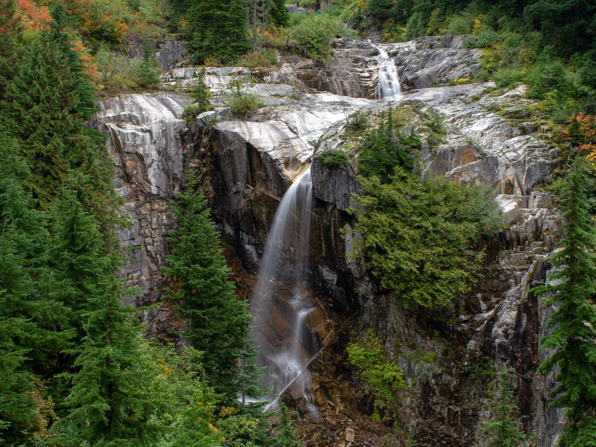 A small waterfall drops in two tiers down a large, rocky cliffside, surrounded by evergreen trees.