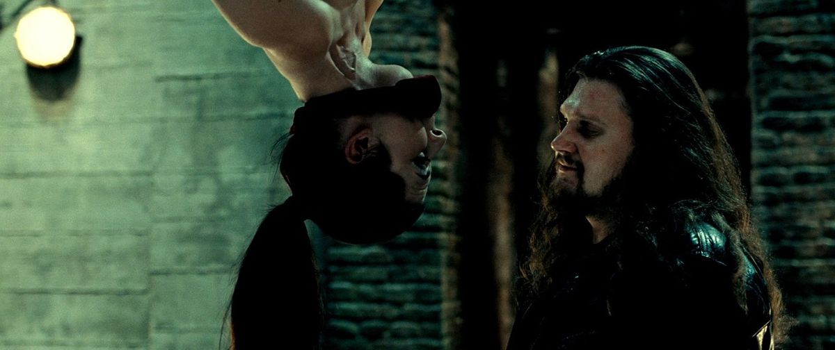 A gagged woman hanging upside down in a dreary grim stone room goes face-to-face with a bearded, long-haired chubby man in black.