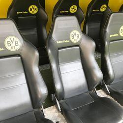 The home bench for Borussia Dortmund. The seats for the home team all sport the logo and the club motto <em>Echte Liebe</em>. August 2, 2019.