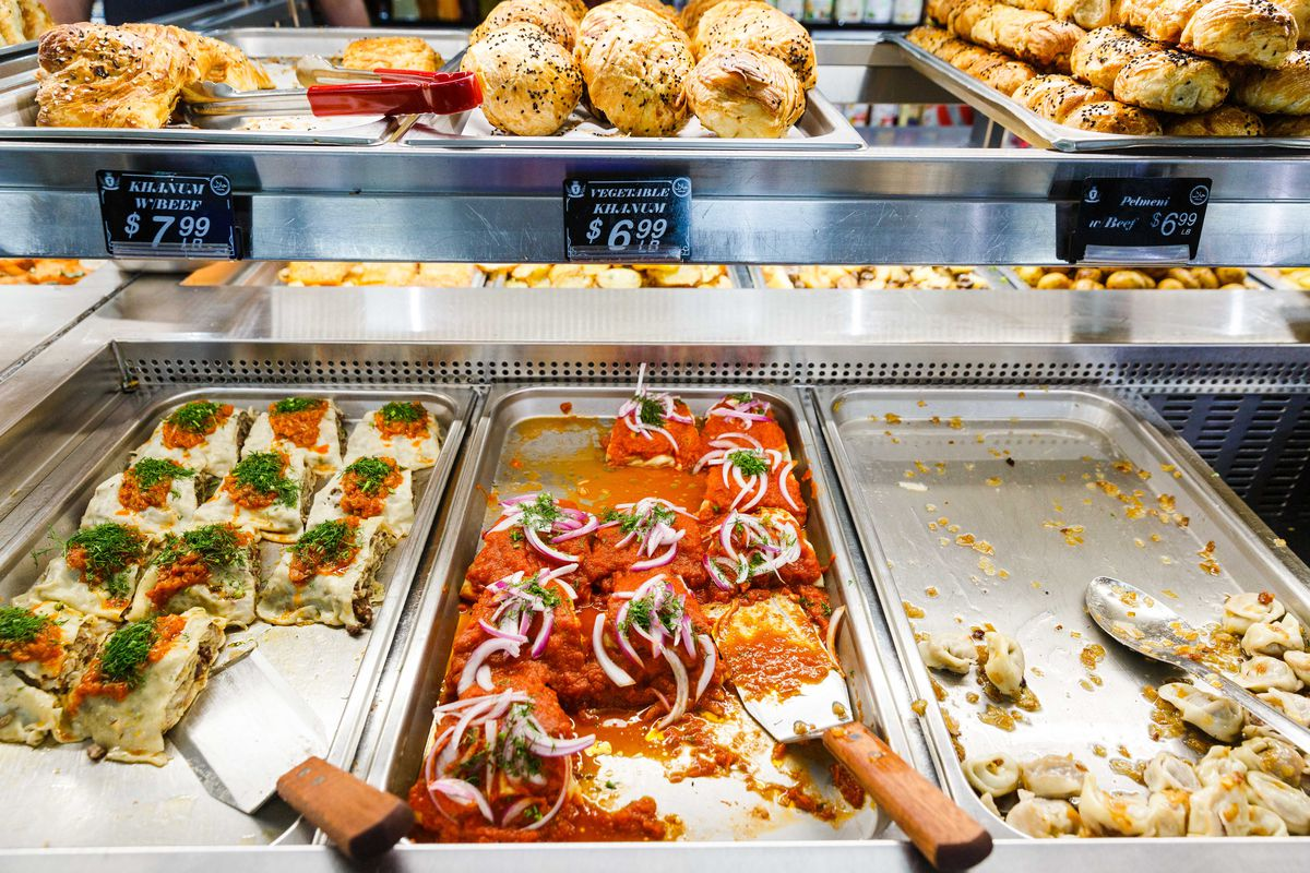 Tomato sauce tops a tray of vegetable hanum, which sits next to meat hanum and other dumplings; the savory fare sit underneath a series of trays holding golden-brown Uzbek pastries, studded with black sesame seeds