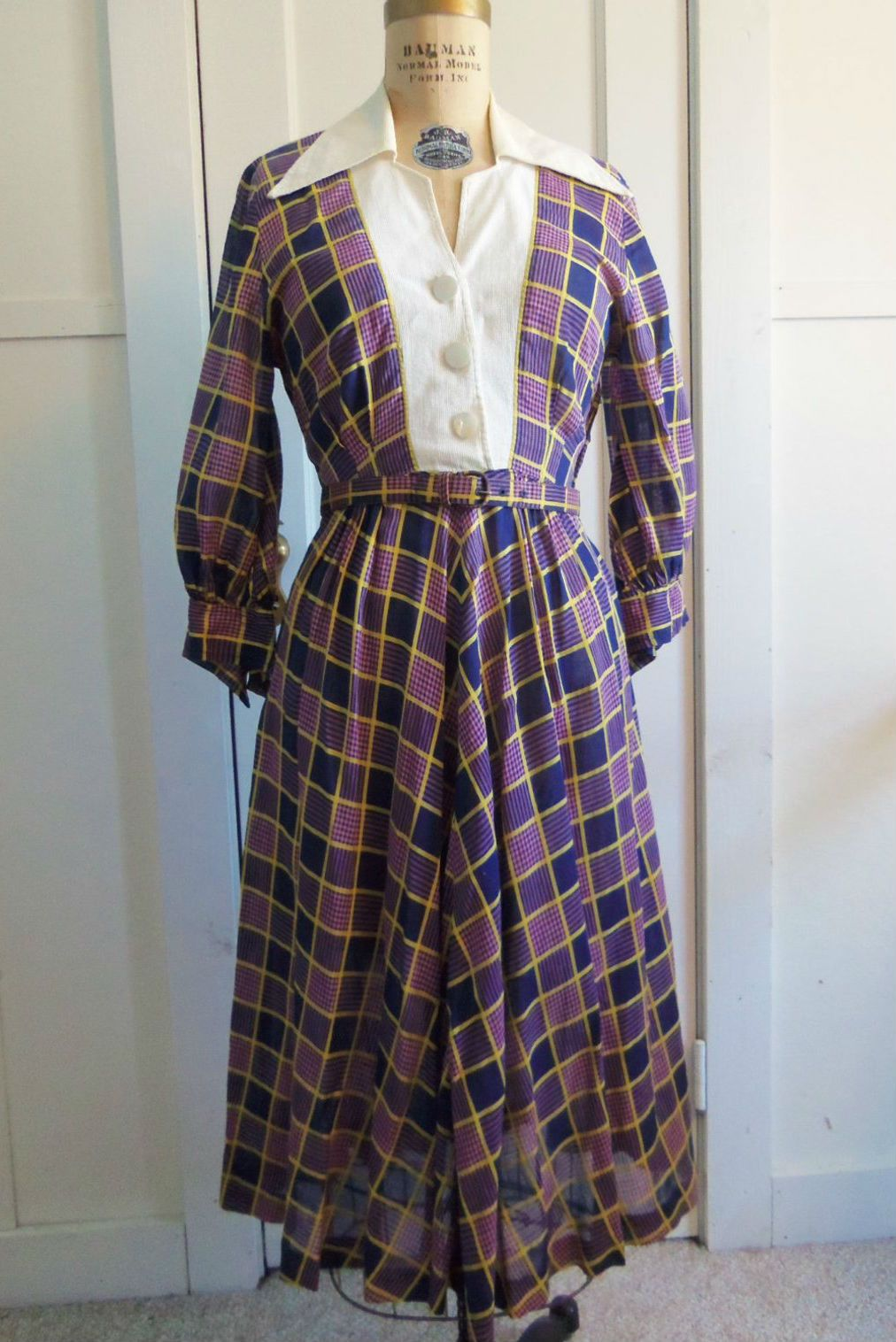 A purple checked dress on a dress form in front of a white door.