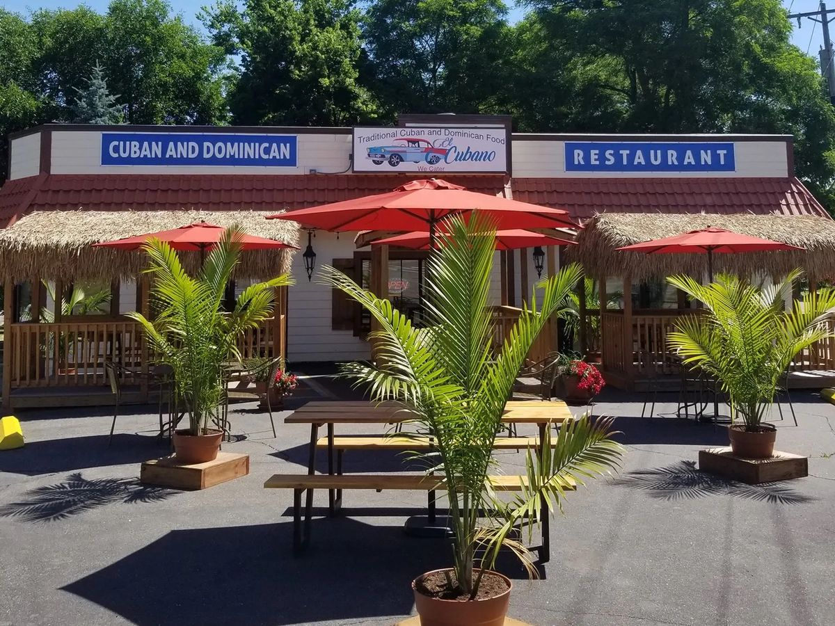The exterior of El Cubano with picnic tables and small palm plants out front