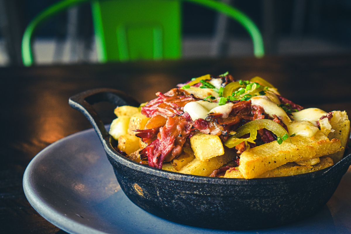 Thick fries sit in a cast iron pan, topped with pieces of beef and melty cheese. There's a green chair in the background.