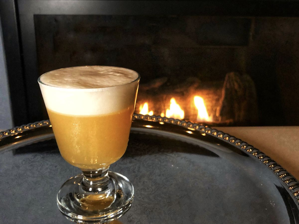 A silver tray positioned by a fire place with a brown drink in a clear glass.
