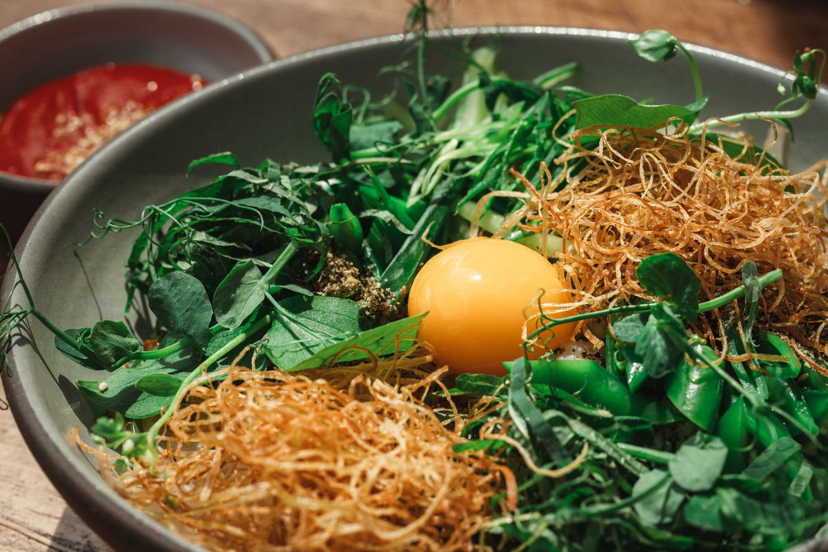 An egg yolk, greens, and thin wispy mushrooms strips are in a bowl