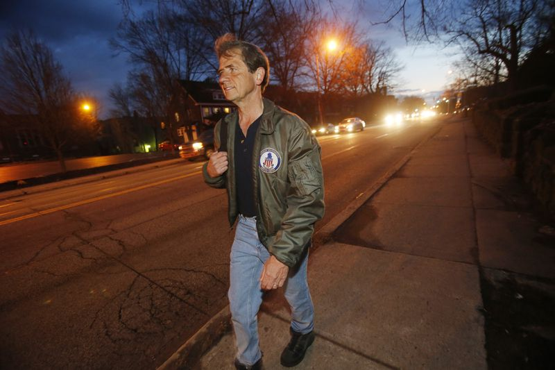 Joe Sestak walks down a Pennsylvania sidewalk as the sun sets and streetlights begin to come on.