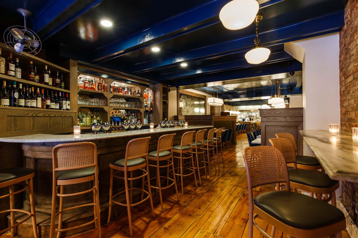 A blue painted sealing, bar seating on either side of the space at marble tables, wooden flooring