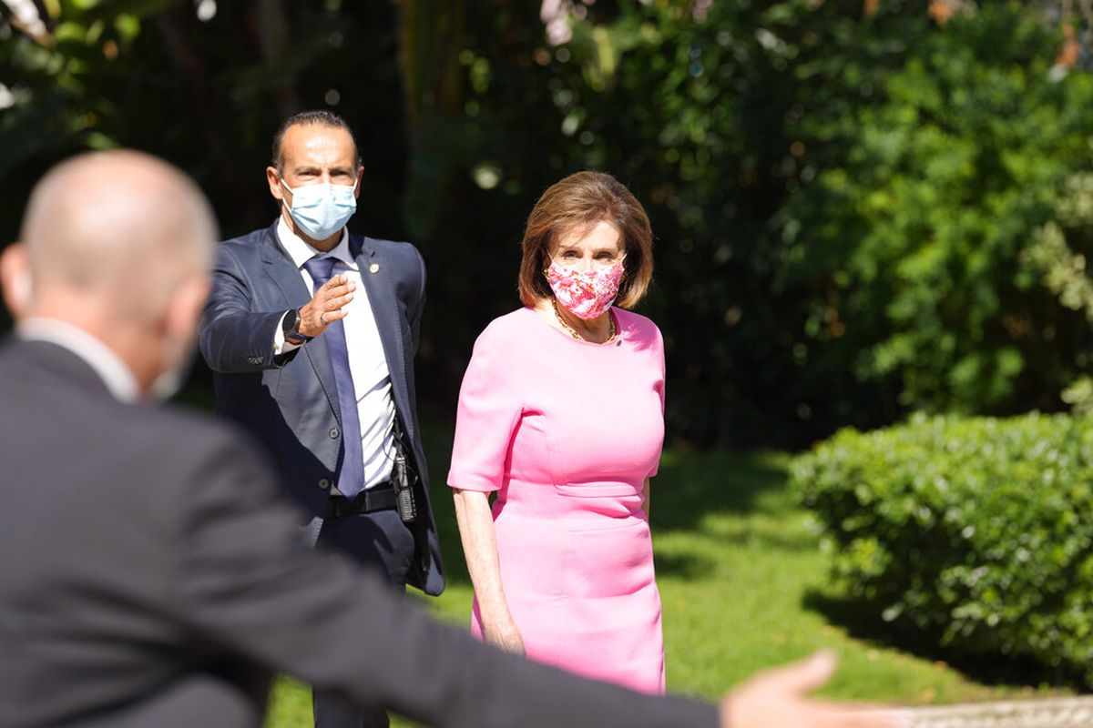 Speaker of the House Nancy Pelosi is directed by security officers in Lisbon, Portugal. Pelosi's visit to a church in Rome was interrupted by protesters.