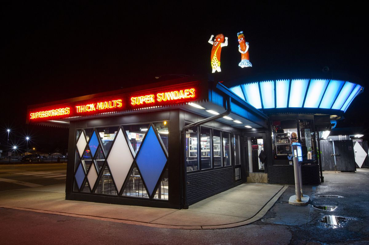 Neon light with words, an art deco styled hot dog stand with two giant hot dogs on top.