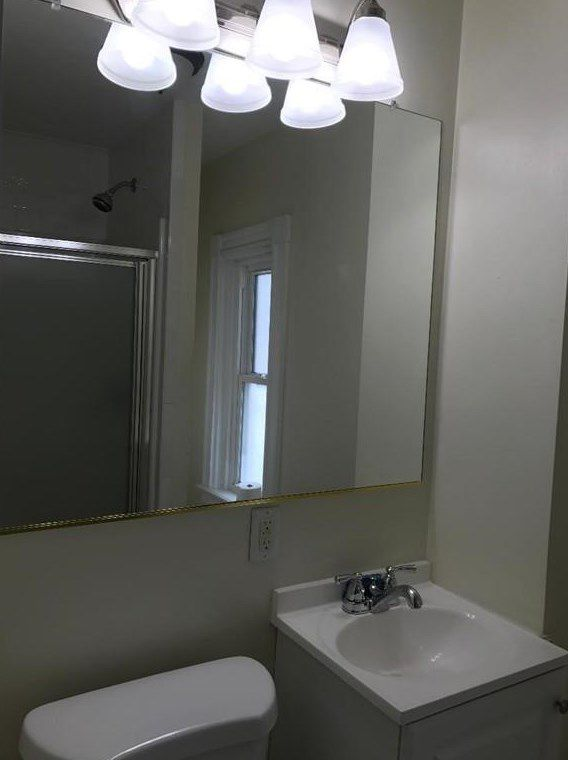 A small bathroom with a large mirror.