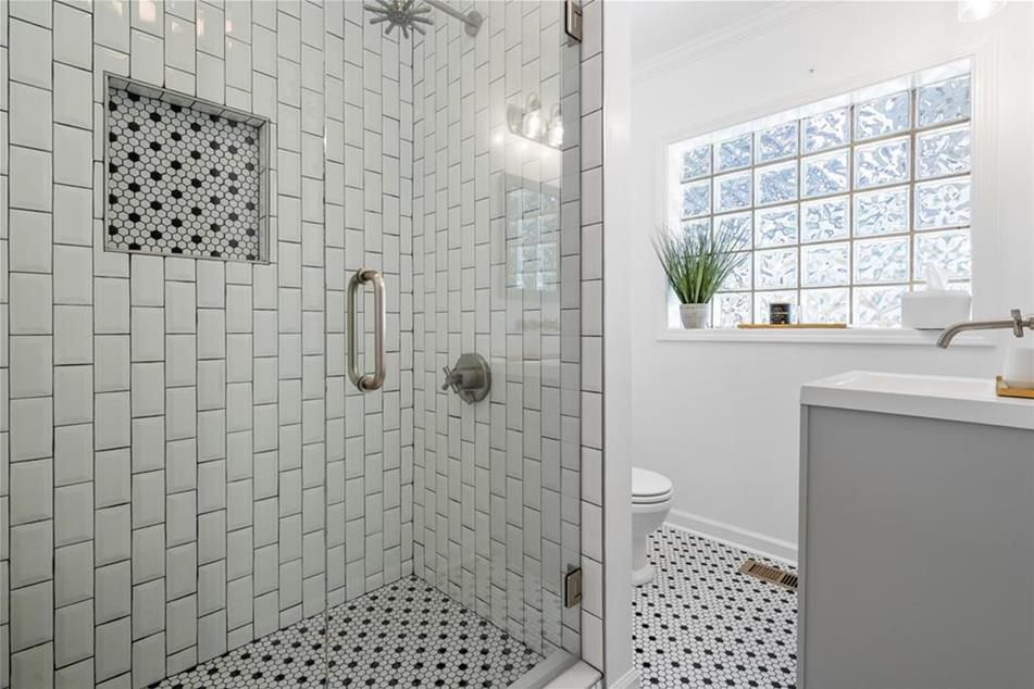 A white bathroom with a  shower at left and sink at right.