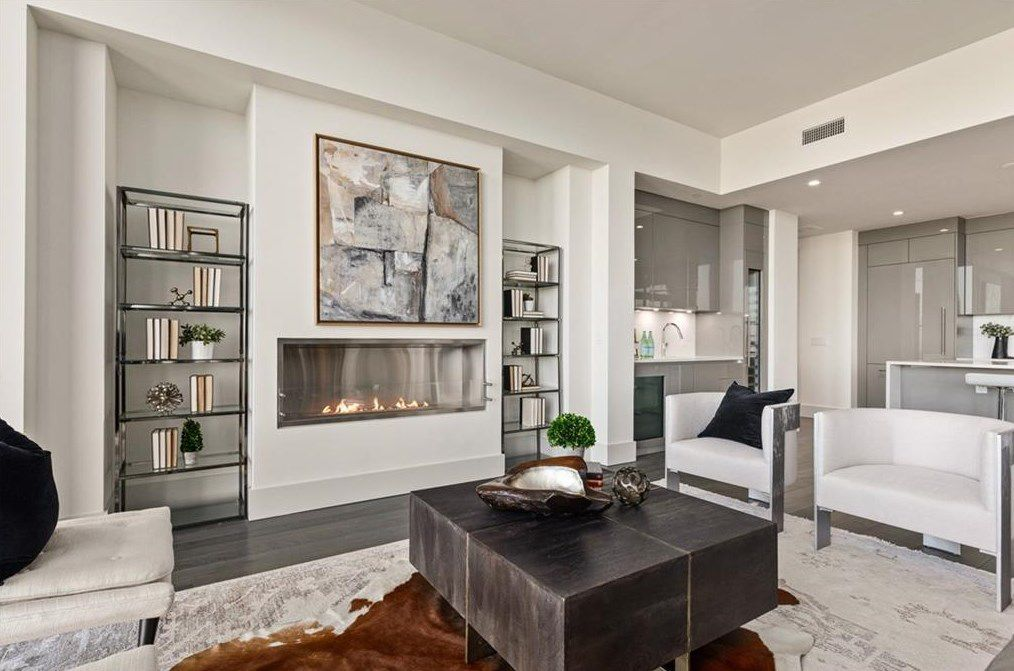 A white living room space with a fireplace and white chairs.